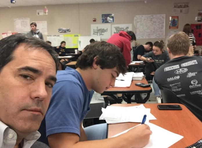 Dieser Vater sitzt neben seinem Sohn im Klassenzimmer