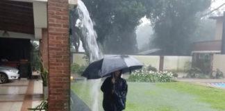 Der Junge steht mit Regenschirm im Gewitter, als ein Blitz einschlägt